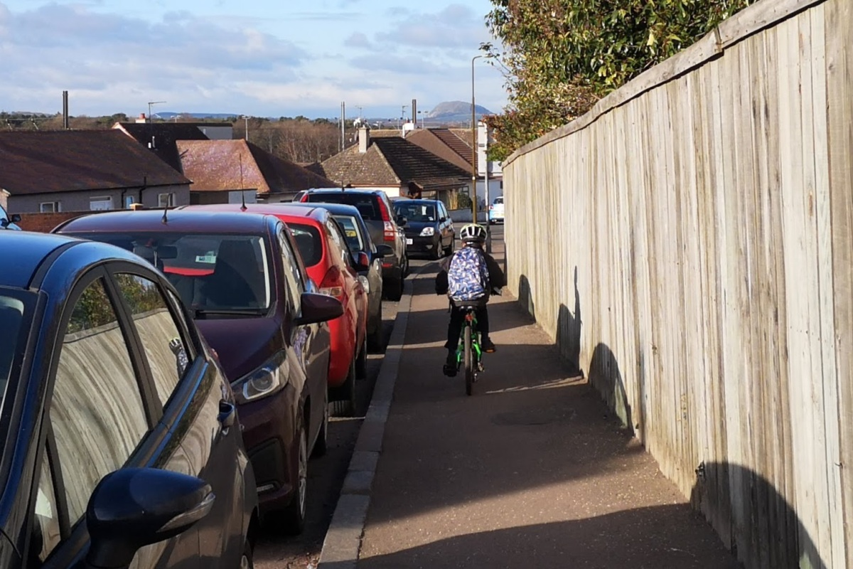young cyclist on pavement with line of parked vehicles alongside